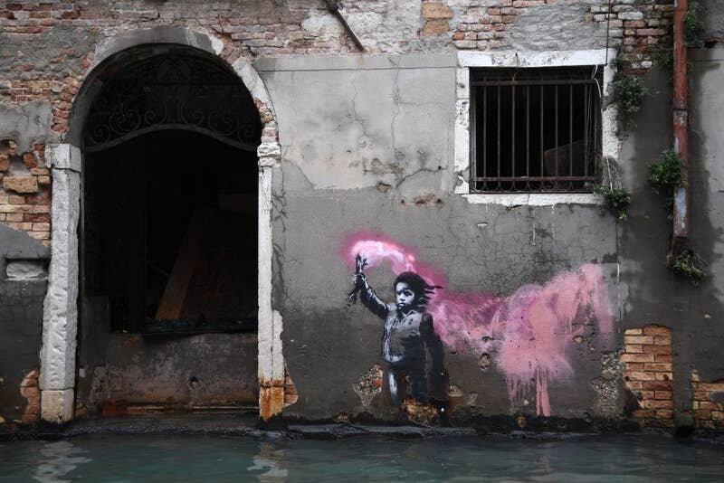 15. Почти затопленная работа Бэнкси на стене одного из зданий - мальчик в спасательном жилете с сигнальным огнем